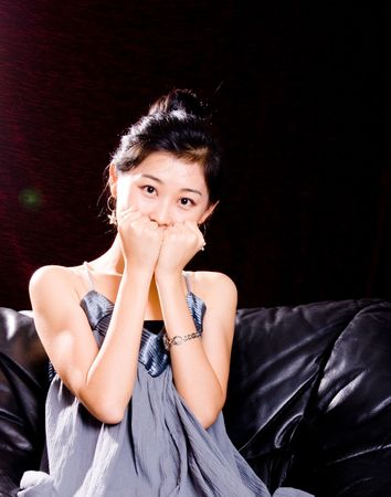blue leather sofa: attractive Asian female model in skirt with smile Stock Photo
