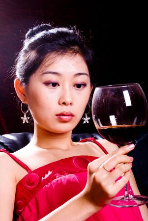 asian female holding goblet with red wine photo