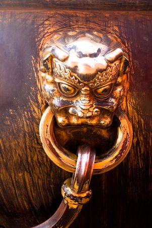 gripe: metal decoration on antique water can in forbidden city