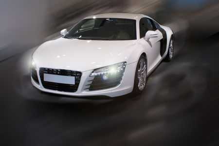 super car: white fancy sports car in motion with front lights on