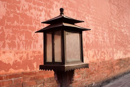 antique wood lamp beside red wall of the forbidden city photo
