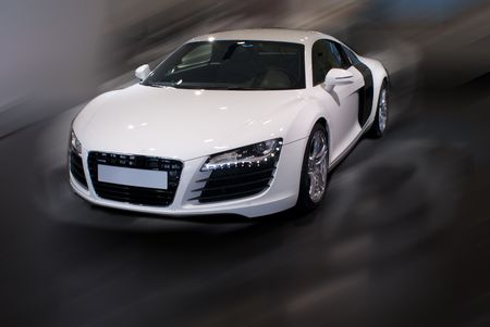 white fancy sports car in motion with front lights off Stock Photo