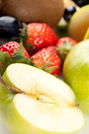 Assorted fresh fruits background including strawberry, apple, kiwi and black and green grape