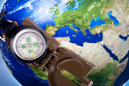 steel compass on travel map of blue globe