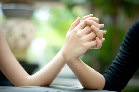 couple holding hands: Beautiful female hands holding together with fingers crossed