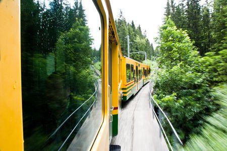 Running yellow train in Switzerland natural forest