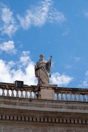 catholicism: Religious Catholicism sculpture on roof against blue sky