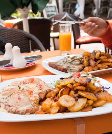 German style meal with potato tomato and steak in white plate