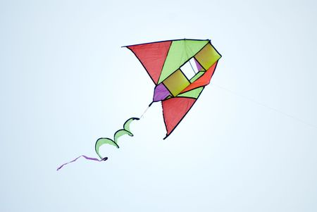 flying a kite: Flying kite in action in the blue sky Stock Photo