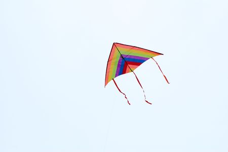 colorful delta kite in action in the blue sky photo