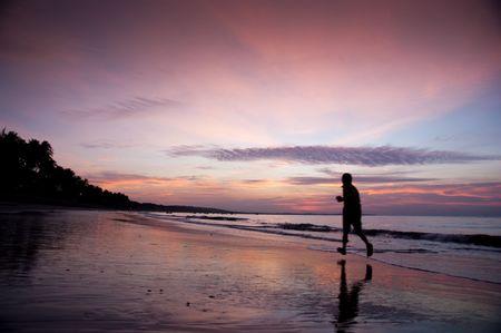 young man run along beach under moring sunrise photo