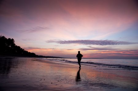 young man run along beach under moring sunrise photo