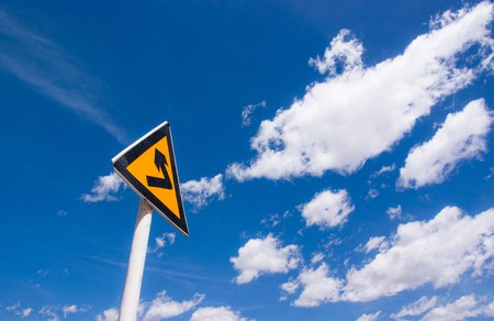 turning sign on yellow metal signboard against blue sky photo