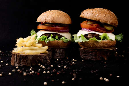 Homemade hamburger with french fries. Peppercorns on a black background.