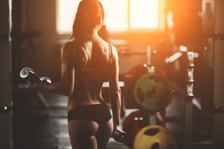 sport training: Brutal athletic woman pumping up muscles with dumbbells. Brunette sexy fitness girl in pink sport wear with perfect body in the gym posing before training set. Attractive fitness woman Stock Photo