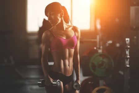 아령으로 근육을 펌핑 잔인한 체육 여자. 핑크 스포츠 갈색 머리 섹시 피트니스 소녀 트레이닝 세트 전에 포즈 체육관에서 완벽한 시체와 함께 착용한