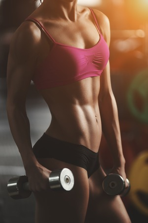 exercise equipment: Brutal athletic woman pumping up muscles with dumbbells. Brunette sexy fitness girl in pink sport wear with perfect body in the gym posing before training set. Attractive fitness woman Stock Photo
