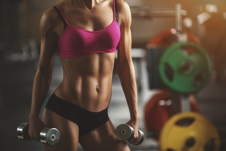 Brutal athletic woman pumping up muscles with dumbbells. Brunette sexy fitness girl in pink sport wear with perfect body in the gym posing before training set. Attractive fitness woman Фото со стока