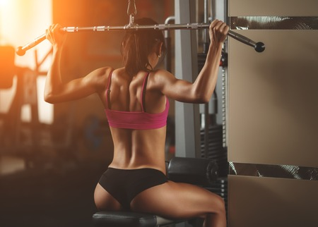 gym room: Brutal athletic woman pumping up muscles with dumbbells. Brunette sexy fitness girl in pink sport wear with perfect body in the gym posing before training set. Attractive fitness woman Stock Photo