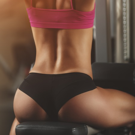 nude ass: Brutal athletic woman pumping up muscles with dumbbells. Brunette sexy fitness girl in pink sport wear with perfect body in the gym posing before training set. Attractive fitness woman Stock Photo