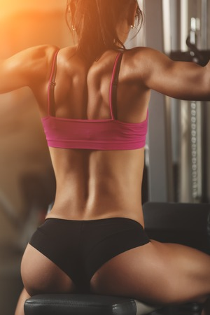 athletics training: Brutal athletic woman pumping up muscles with dumbbells. Brunette sexy fitness girl in pink sport wear with perfect body in the gym posing before training set. Attractive fitness woman Stock Photo