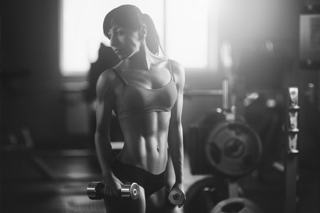 Black and white photo of a strong woman. Brunette sexy fitness girl in sport wear with perfect body in the gym posing before training set