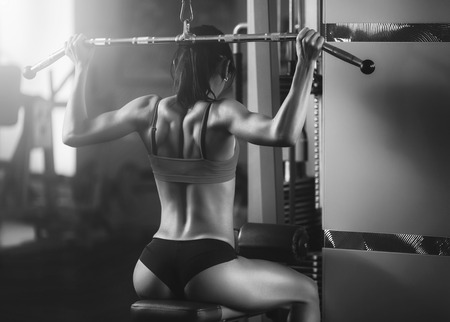 sport wear: Black and white photo of a strong woman from behind. Brunette sexy fitness girl in sport wear with perfect body in the gym posing before training set. Attractive fitness woman, trained female body Stock Photo