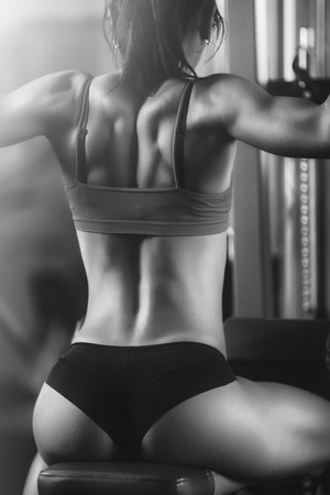 Black and white photo of a strong woman from behind. Brunette sexy fitness girl in sport wear with perfect body in the gym posing before training set. Attractive fitness woman, trained female body Stock Photo