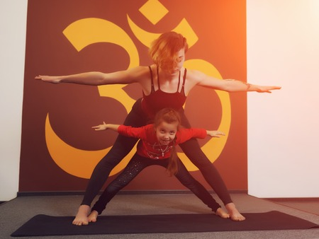 Mother and child yoga practice on the background of the Indian symbol of OM. Beautiful young mother with little daughter doing yoga. Sports family photo