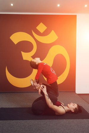 sanskrit: Mother and child yoga practice on the background of the Indian symbol of OM. Beautiful young mother with little daughter doing yoga. Sports family