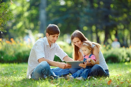 Happy family of three people resting in a city park with a tablet in hands. Father shows in tablet funny pictures. Family sitting on grass and looking at the tablet. Happy family concept of the good life.