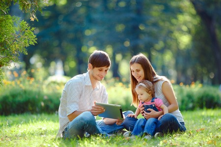 Happy family of three people resting in a city park with a tablet in hands. Father shows in tablet funny pictures. Family sitting on grass and looking at the tablet. Happy family concept of the good life. photo