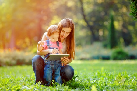 family with three children: Beautiful mother and kid girl playing at tablet pc outdoors in fall. Happy mother showing her daughter funny pictures your tablet. Happy family, mother and daughter with tablet resting in the park. Stock Photo