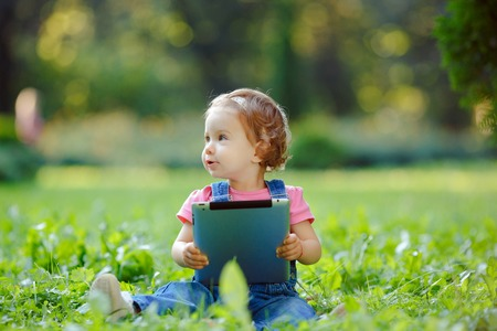Child playing with tablet outdoors. Cheerful child with a portable PC in your hands. The kid looks away. photo