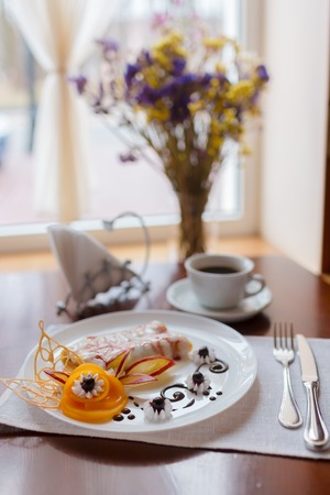 Pancakes with cherry jam beautifully decorated with flowers of fruit and chocolate on a white plate, which stands on a wooden table near the window in the interior cozy cafe. Shallow depth of field. photo