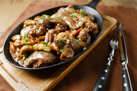 Liver baked with mushrooms, bacon and herbs in a frying pan on a wooden board closeup close lie knife and fork
