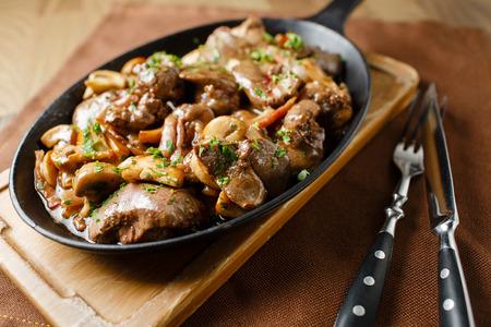 higado de pollo: H�gado horno con setas, tocino y las hierbas en una sart�n sobre una tabla de madera close mentira cuchillo y tenedor Foto de archivo
