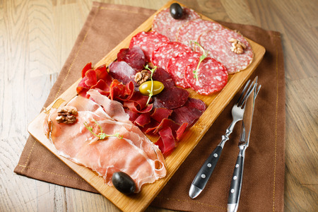 Variety of meats, sausages, salami, ham, olives, laid out on a wooden board close-up, horizontal, are next to a knife and fork photo