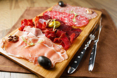 ham: Variety of meats, sausages, salami, ham, olives, laid out on a wooden board close-up, horizontal, are next to a knife and fork