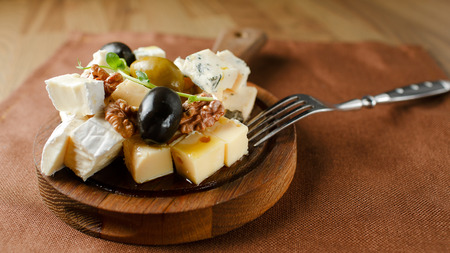 tabla de quesos: Variedad de queso con frutos secos y aceitunas distribuida en una tabla de madera. Fondo de alimentos con el vino Foto de archivo