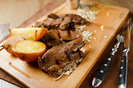 baked meat: Baked meat with potatoes and onions on a wooden board