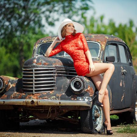 vestidos antiguos: Mujer joven hermosa que se ve sexy, viene contra el telón de fondo de un viejo coche negro en un vestido rojo. Chica en vestido rojo que sostiene un sombrero blanco. Imagen de una mujer que mira hacia otro lado. Foto de archivo