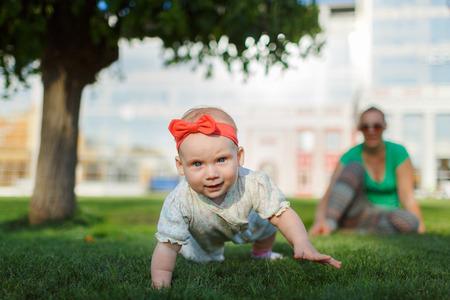 bebe gateando: Beb� que se arrastra en la hierba en un fondo de sentarse mam�