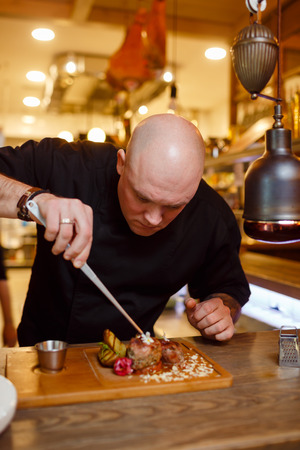 piatto di carne: Chef in a black uniform jacket is working on a meat dish