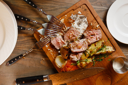 Meat dish natural appearance. Appetizing slices of meat, sliced on a wooden board with a side dish of baked potato and onion slices, sprinkle with spices, black pepper, seeds and garlic photo