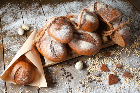 Variety of rye bread on a wooden background with flour, grain and quail eggs