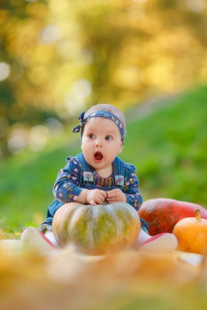 Little girl in jeans sundress sitting near the pumpkin on a background autumn forest. Cheerful child playing outdoors, lying near the pumpkin.