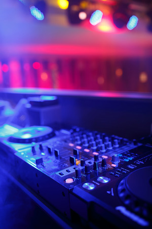 dj: DJ mixer with light colored spotlights discos, shallow depth of field and beautiful swirling bokeh Stock Photo