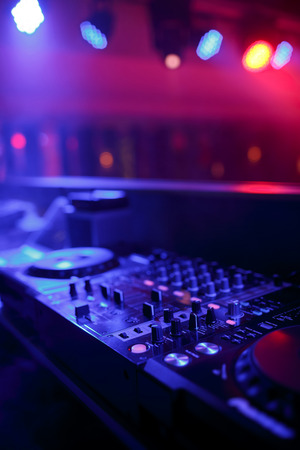 DJ mixer with light colored spotlights discos, shallow depth of field and beautiful swirling bokeh photo