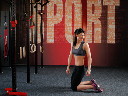 caucasian appearance: Crossfit workout on ring. Fit woman holds training session crossfit on the rings in the gym. Attractive muscular woman, caucasian appearance, brunette is kneeling in the gym and looking to the side